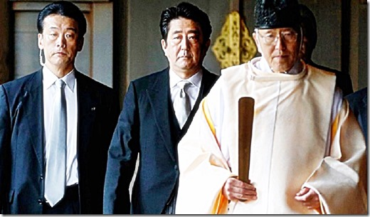 Japan's Prime Minister Shinzo Abe (C) is led by a Shinto priest as he visits Yasukuni shrine in Tokyo December 26, 2013.