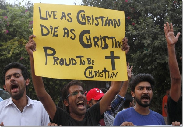 A member of the Pakistani Christian community holds a placard as he shouts slogans during a protest rally to condemn Sunday's suicide attack in Peshawar on a church, with others in Lahore September 23, 2013