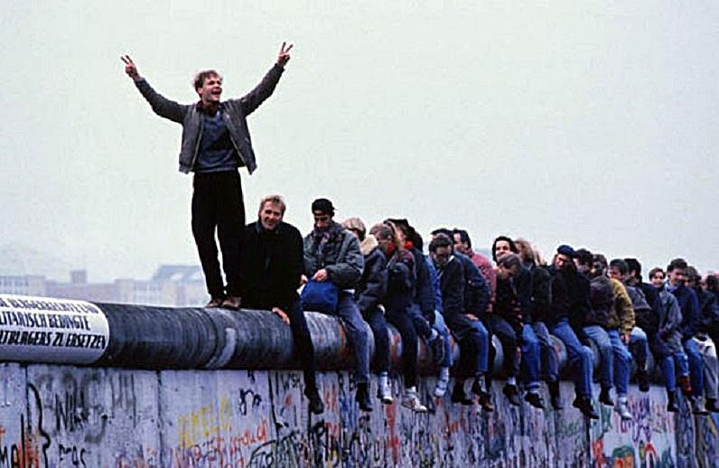 People celebrating atop Berlin Wall